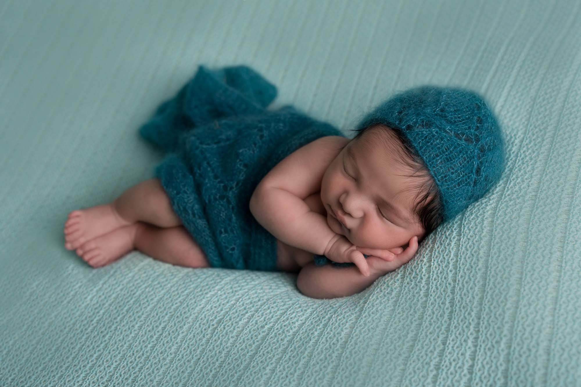 newborn little boy in side pose in green hat on a green blanket background