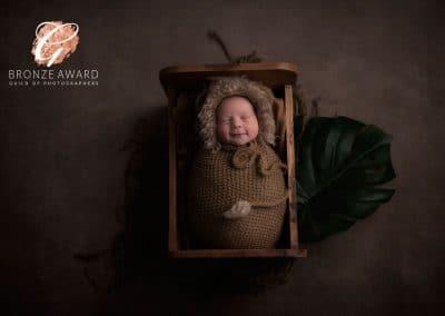 newborn baby in bed brown lion