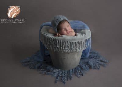 newborn baby boy in a bucket and hat