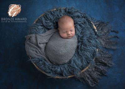newborn baby boy in blue fur basket