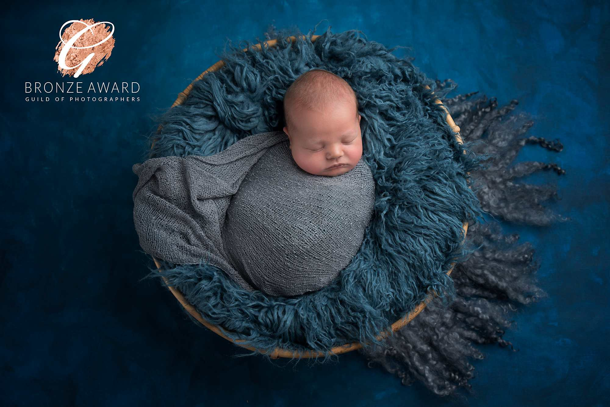 newborn baby boy in blue fur basket