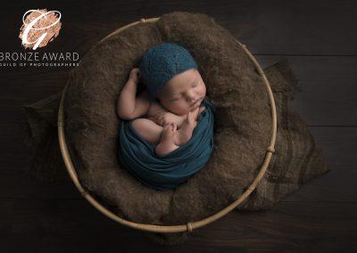 little newborn baby boy in a brown basket