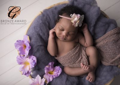newborn baby girl with flowers in a basket