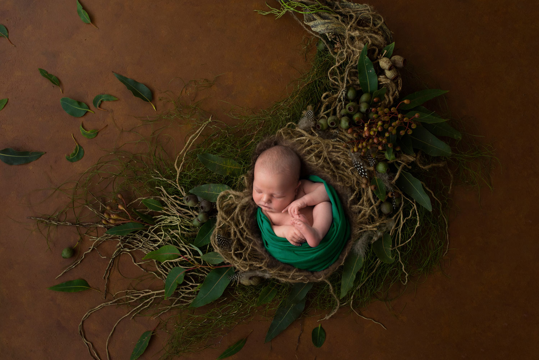 baby boy on green blanket in nest of sticks by Newborn Photographer Cheshire
