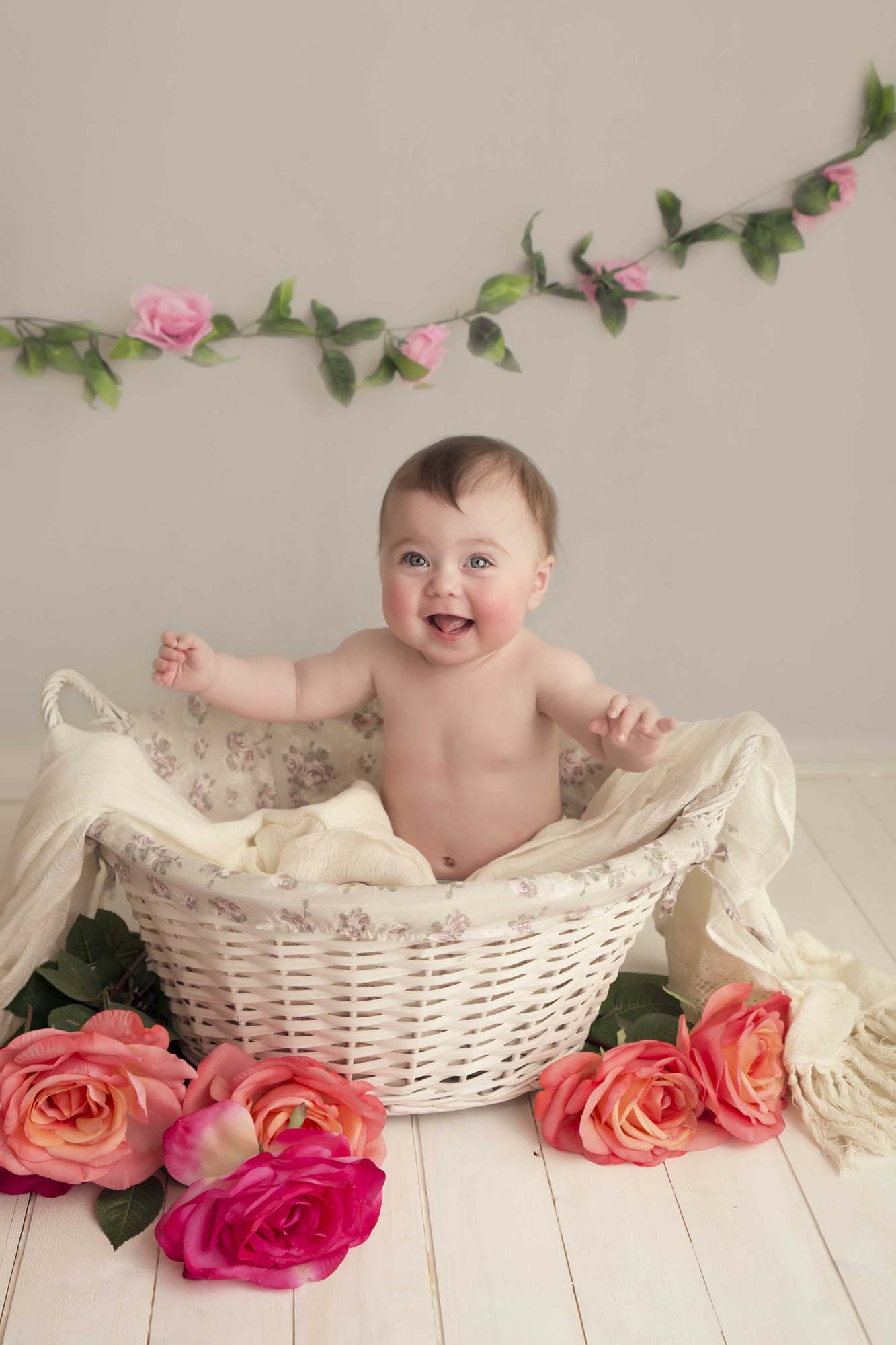baby girl sitting in basket with flowers photographed by Baby Photographer Manchester