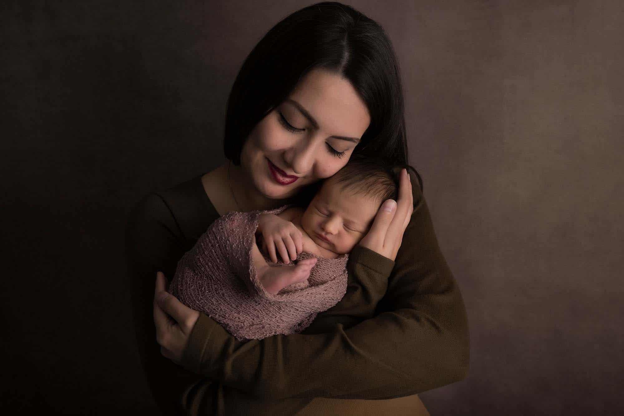 mummy with newborn baby on brown background in studio by Newborn Photographer Cheshire