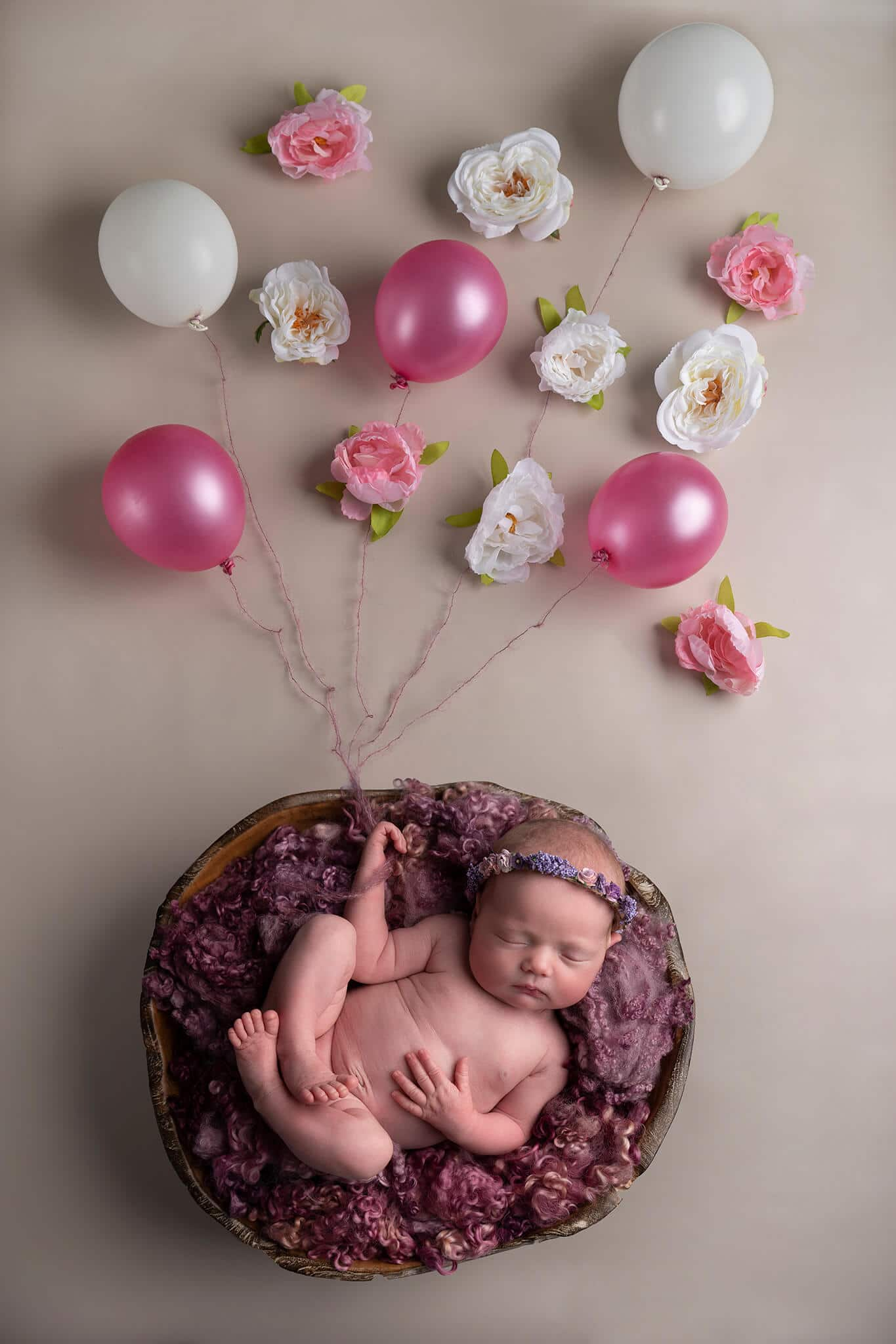 Newborn baby girl in bowl with balloons photographed by Newborn Photographer Cheshire