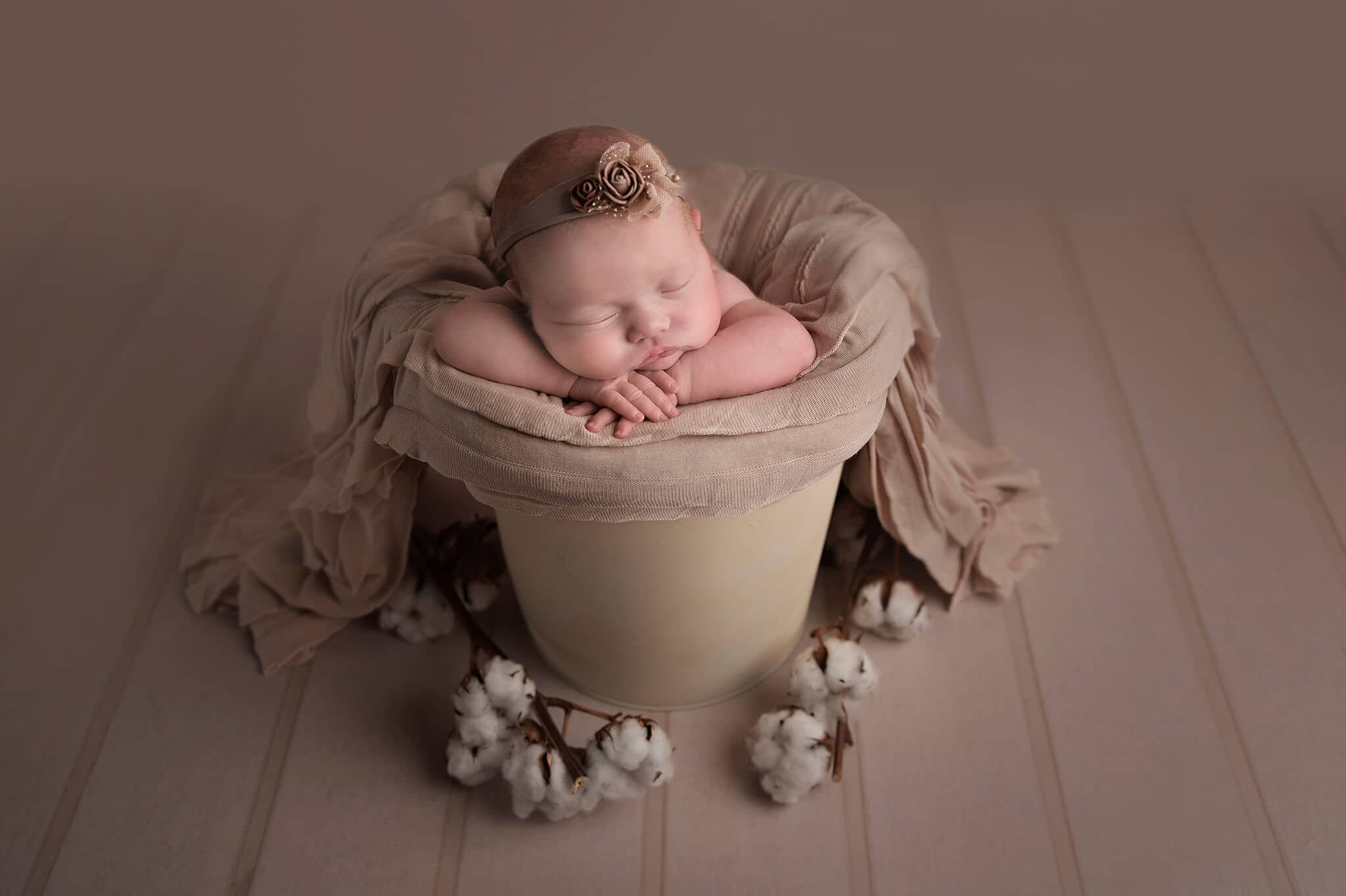 baby girl in bucket with beige blanket by Newborn Photographer Cheshire