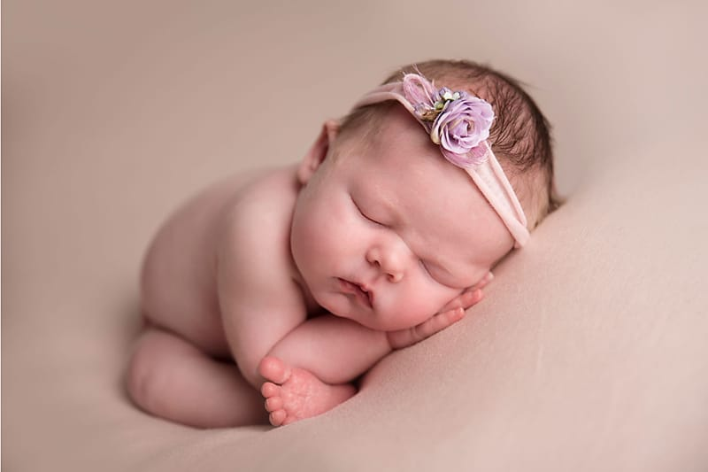 newborn baby in taco pose