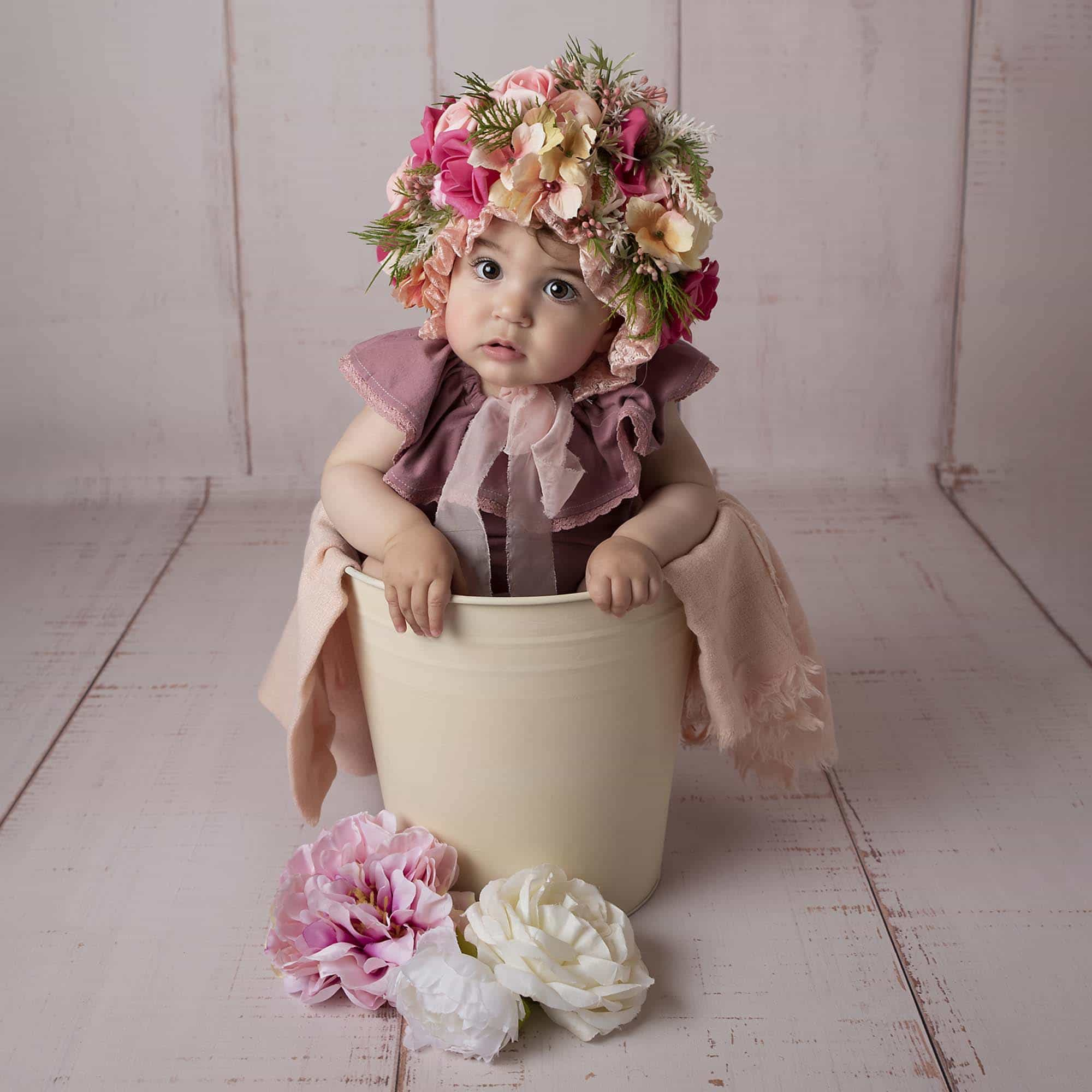 baby photoshoot baby sitting in bucket with flower bonnet