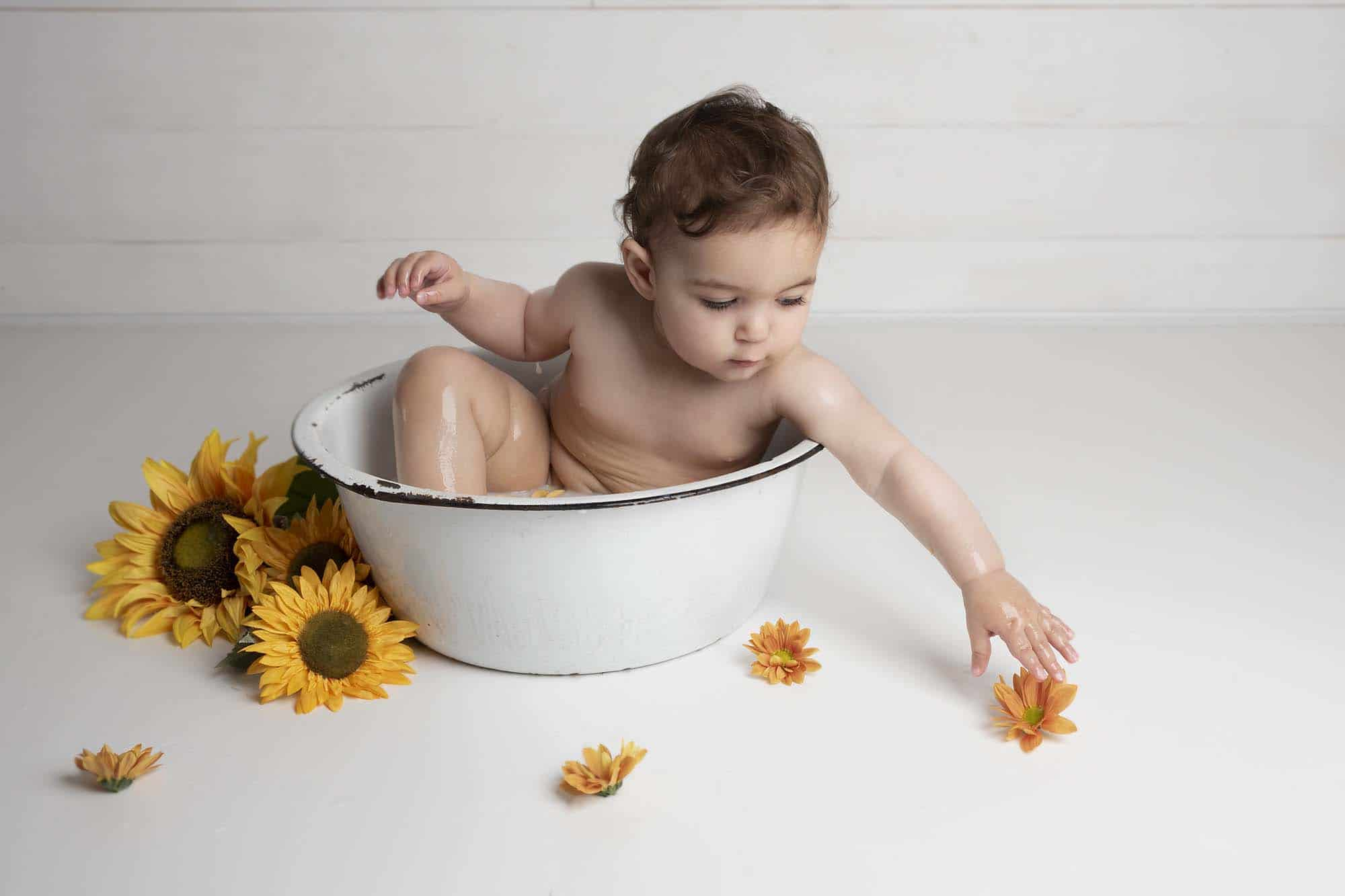 one year old sitting in a bowl with flowers