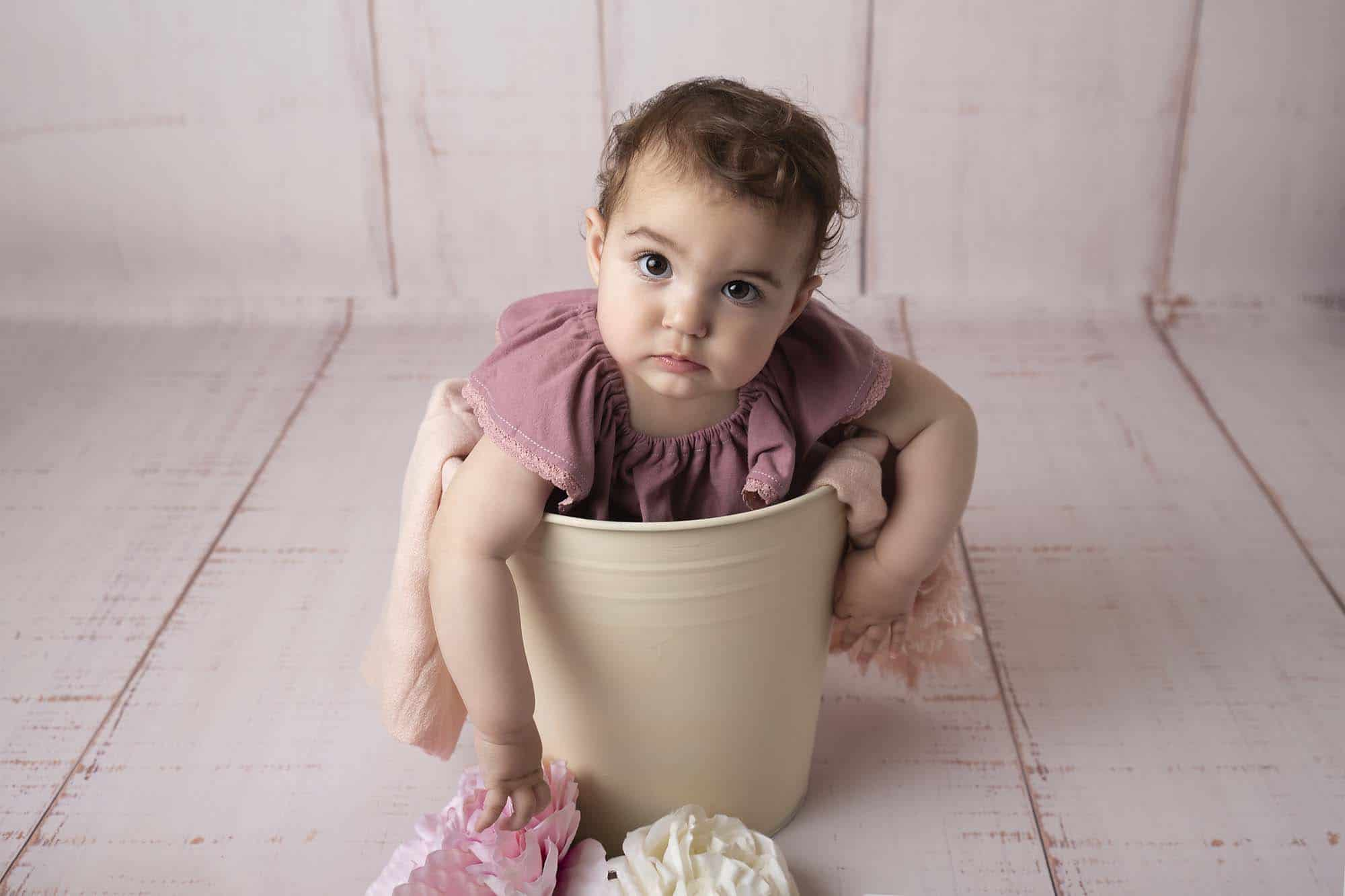 one year old girl in pink dress sitting in a bucket