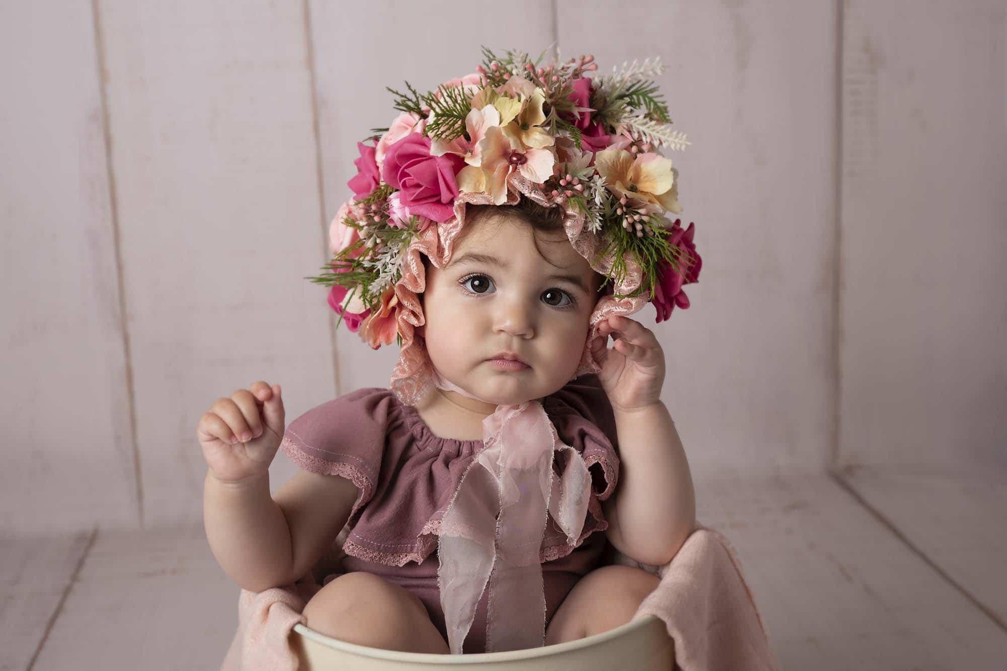 baby photoshott little girl is sitting in a bucket and wearing a flower bonnet on her head