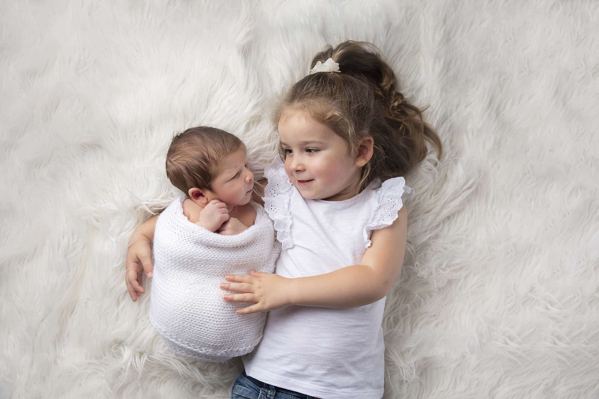sibling little girl with newborn boy on white fur photographed by Newborn Photographer Manchester