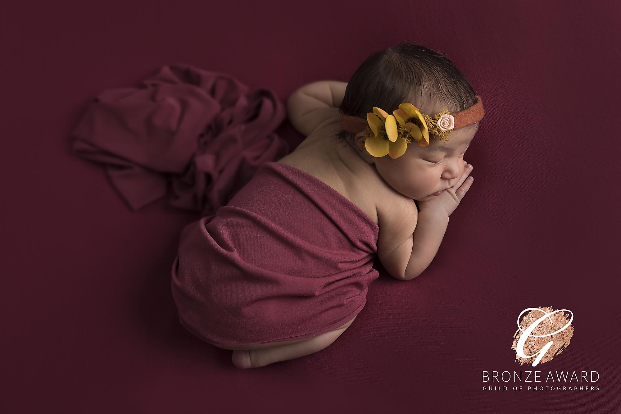 newborn baby girl on red blanket photographed by Newborn Photographer Manchester