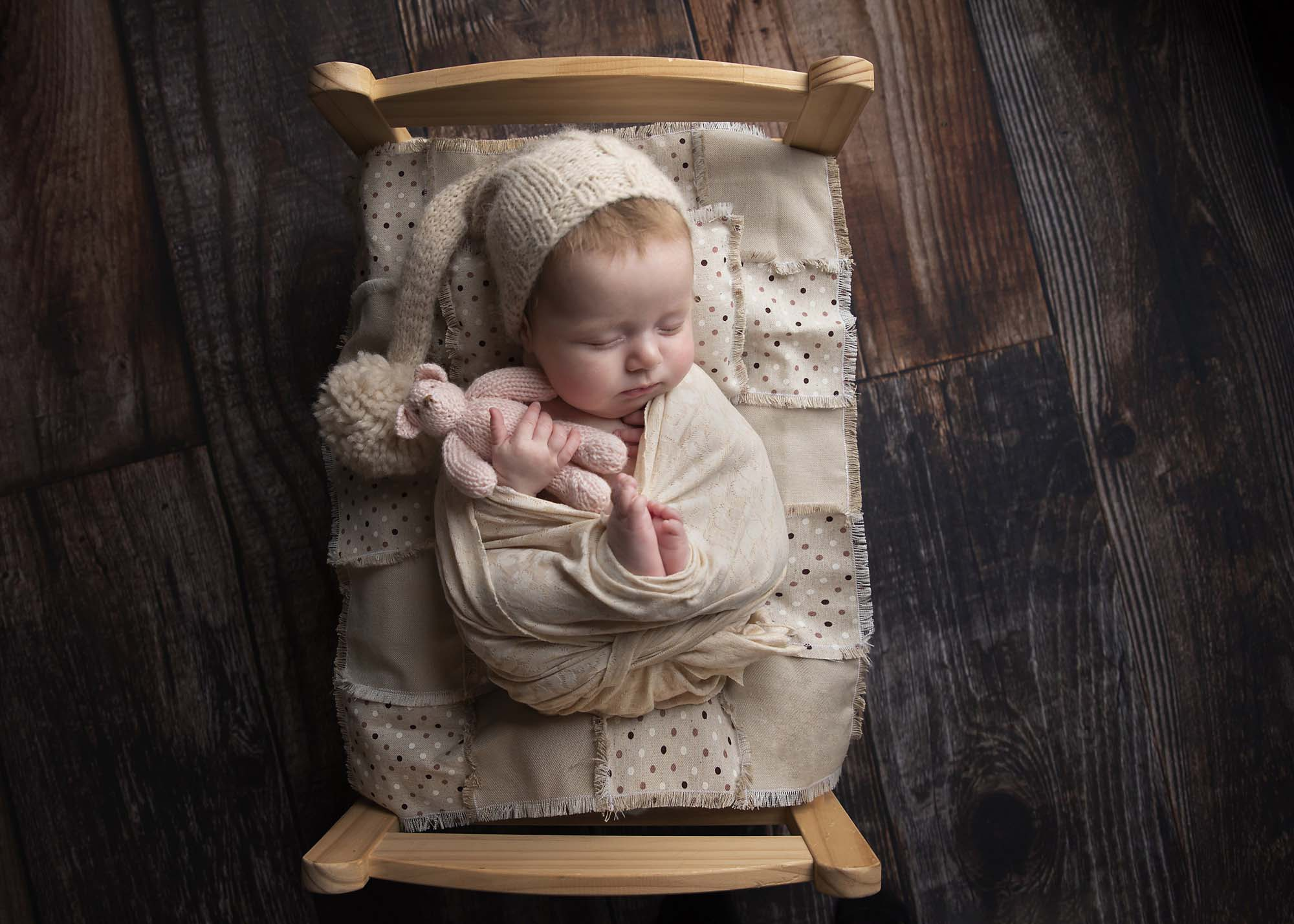 newborn baby girl sleeping on a bed holding teddy photographed by Newborn Photographer Manchester