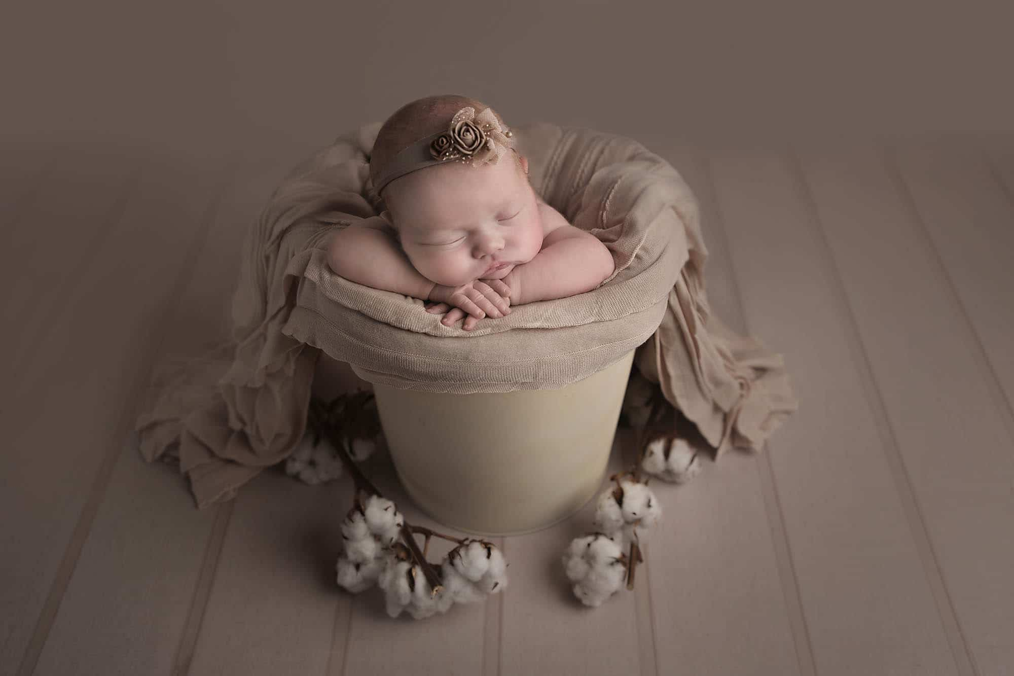 newborn girl in brown bucket photographed by Newborn Photographer Manchester