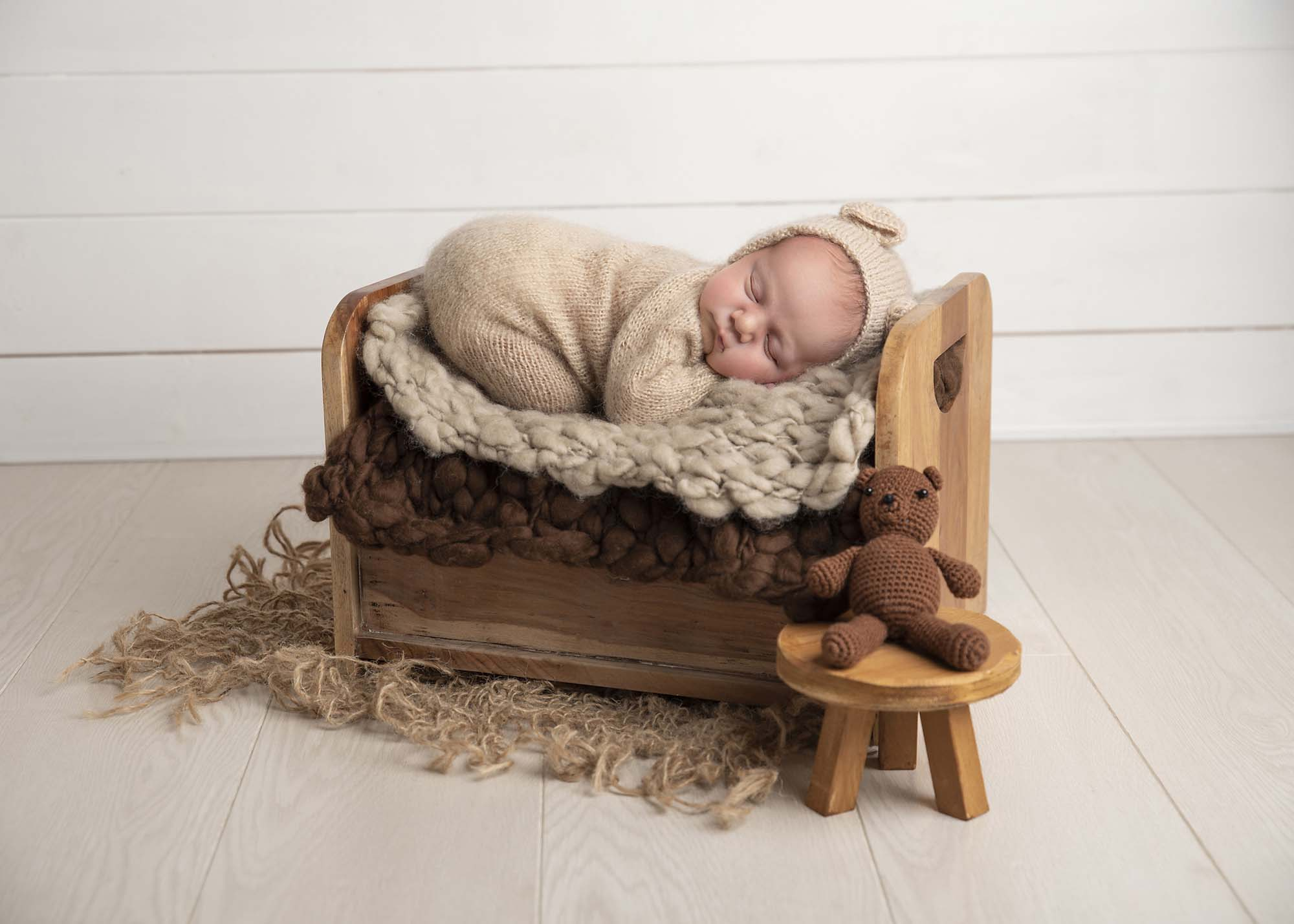 newborn baby boy sleeping on a bed with teddy outfit photographed by Newborn Photographer Manchester