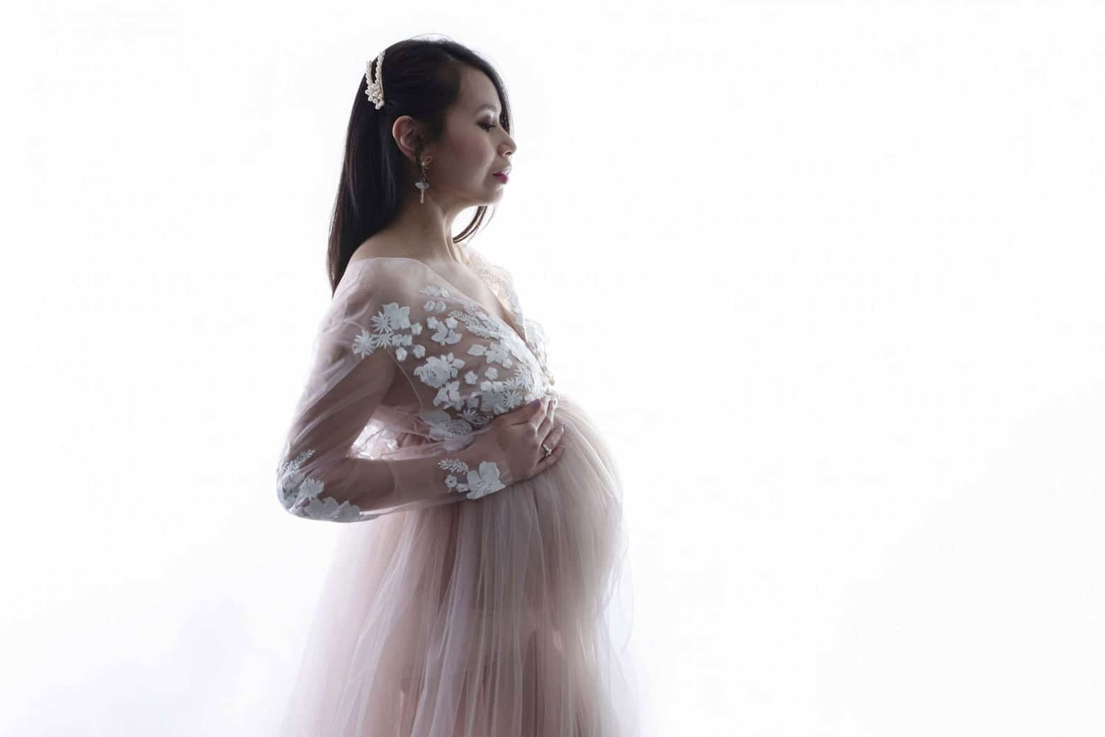 maternity photoshoot in a studio in white dress and background photographed by Newborn Photographer Manchester