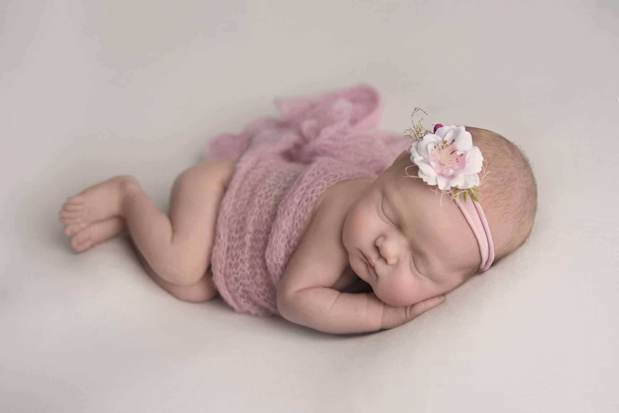 newborn girl sleeping on white blanket photographed by Newborn Photographer Cheshire