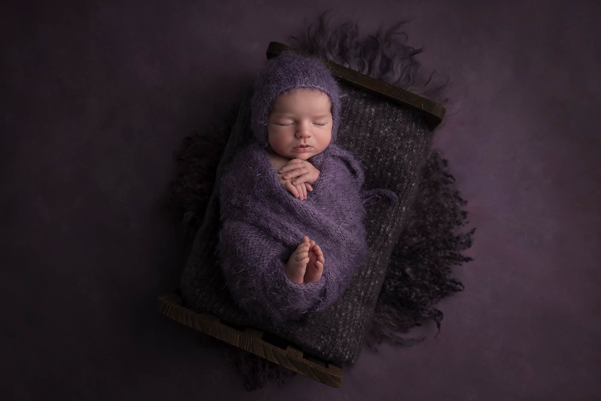 newborn girl with purple background photographed by Newborn Photographer Cheshire