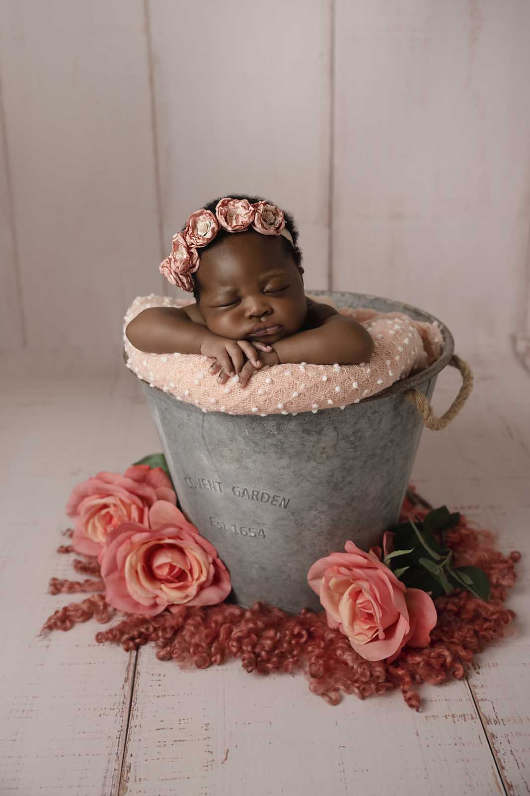 newborn girl in bucket with roses photographed by Newborn Photographer Cheshire