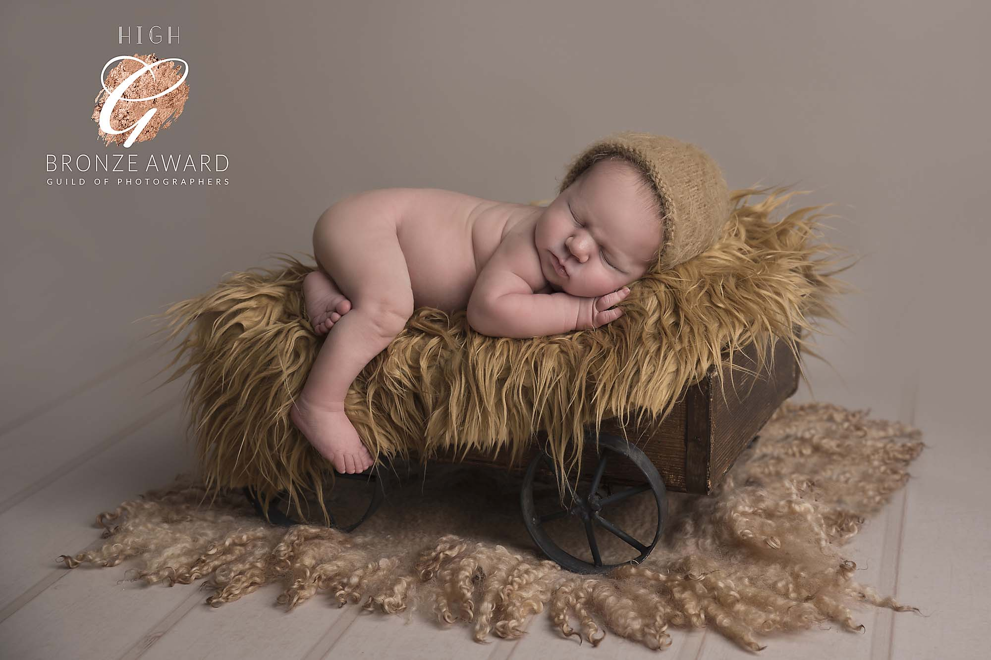 newborn baby boy on a wooden carriage photographed by Newborn Photographer Cheshire