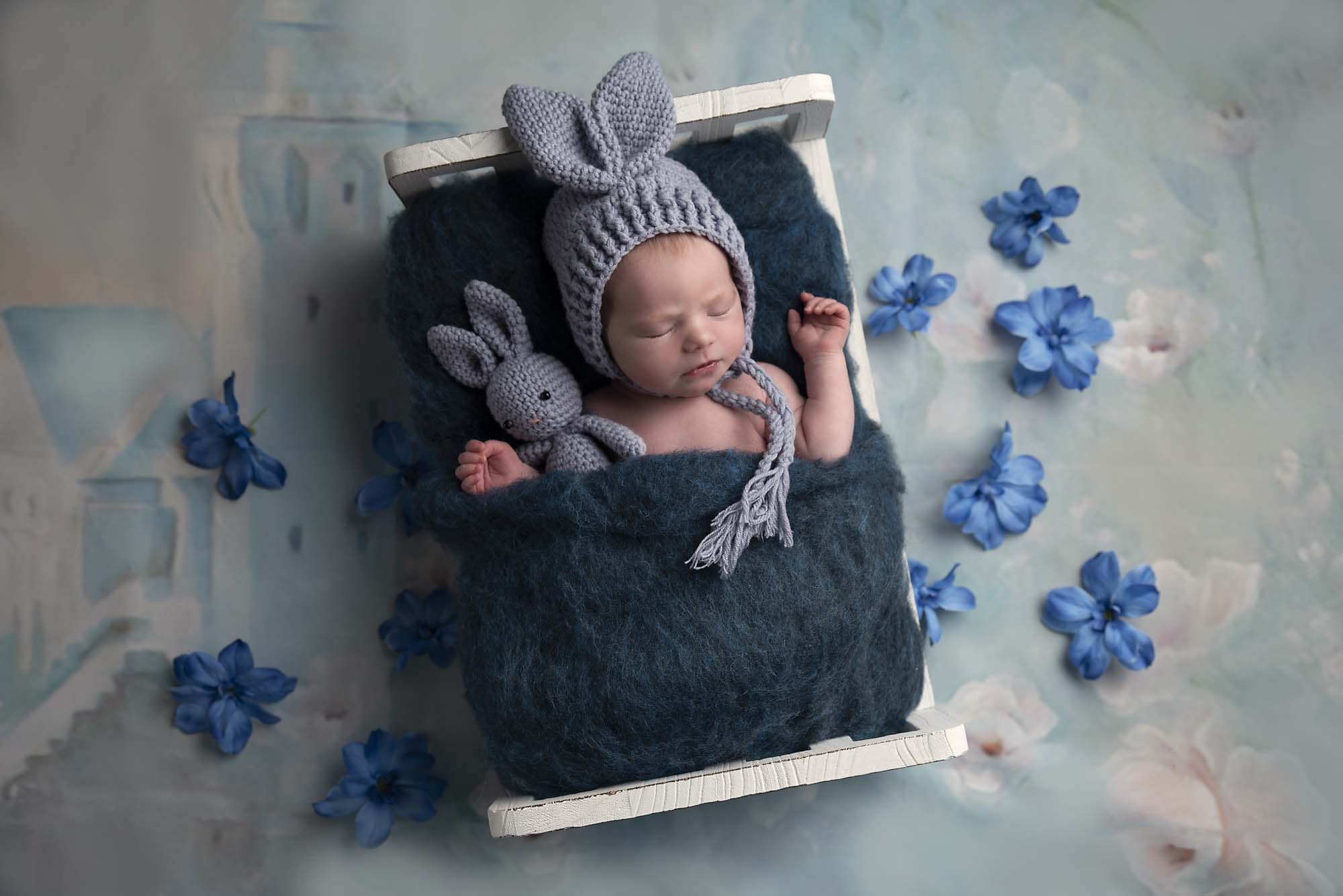 newborn girl in bed with bunny hat photographed by Newborn Photographer Cheshire