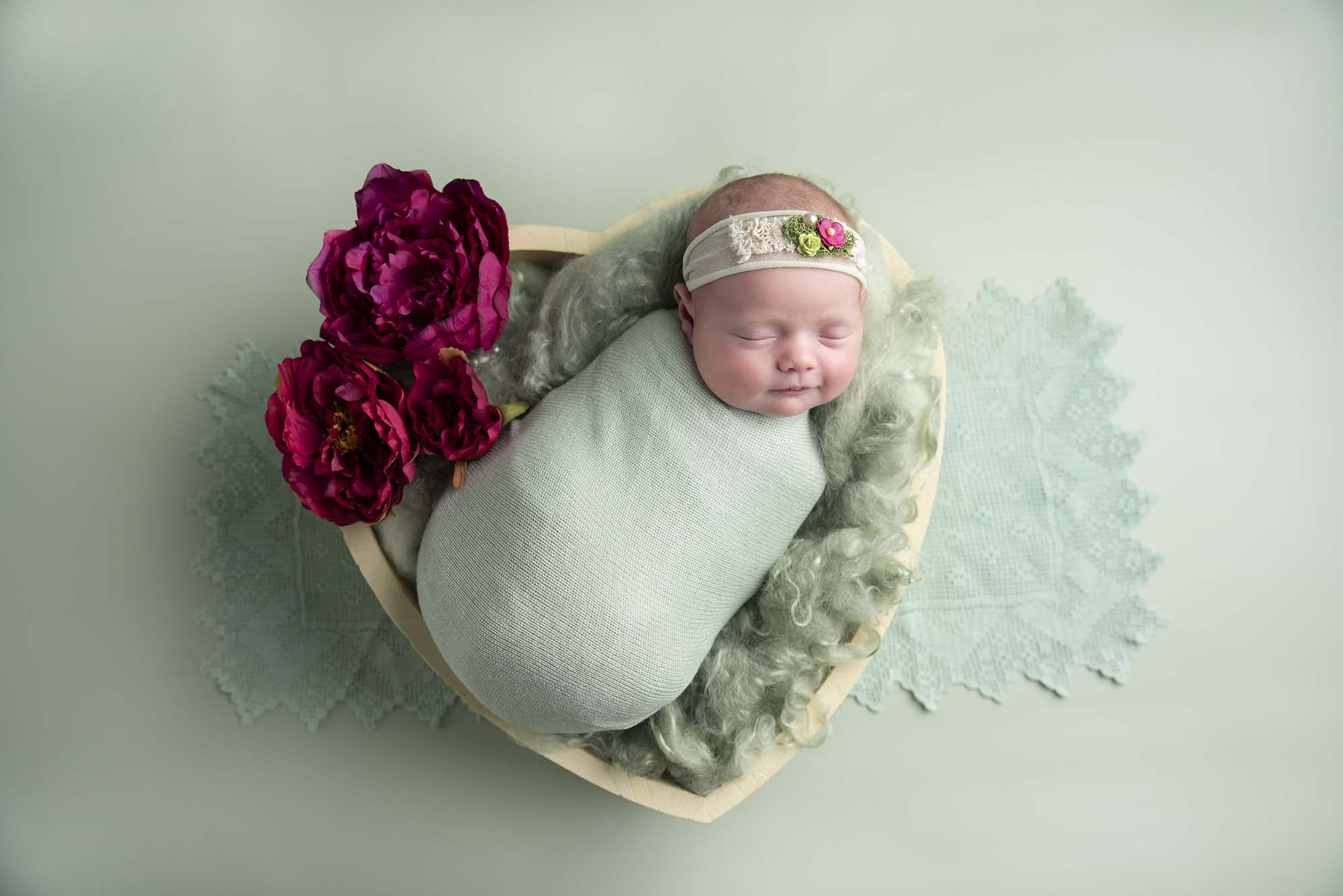 newborn girl in hear shape bowl photographed by Newborn Photographer Cheshire