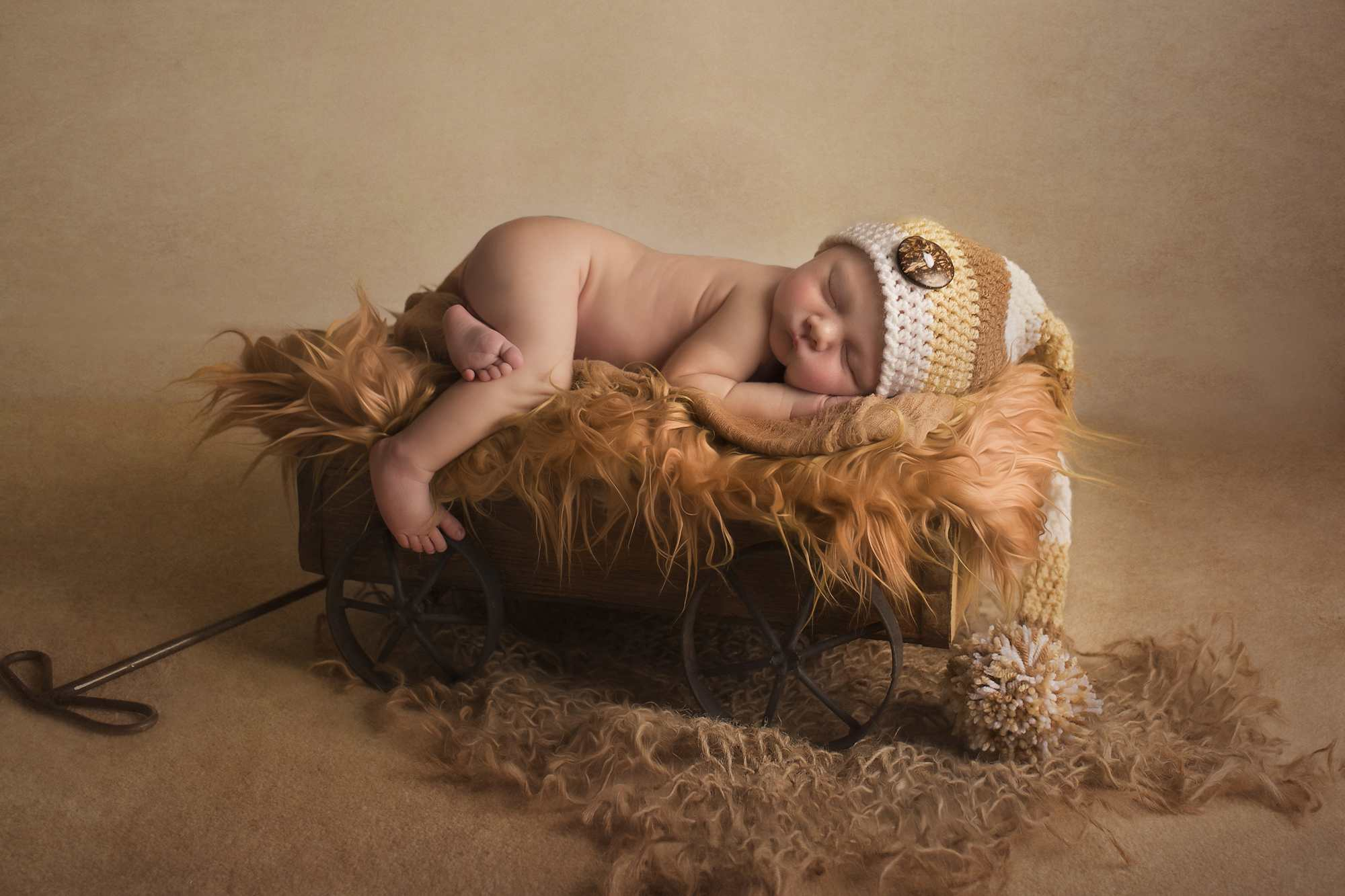 newborn boy on brown carriage photographed by Newborn Photographer Cheshire