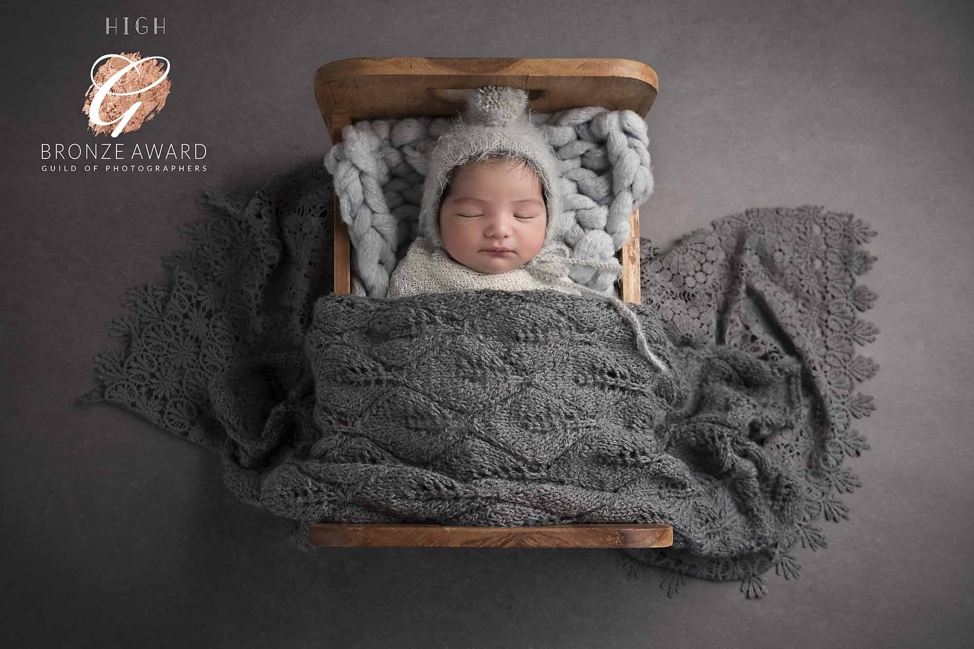 newborn boy in bed with grey blanket photographed by Newborn Photographer Cheshire