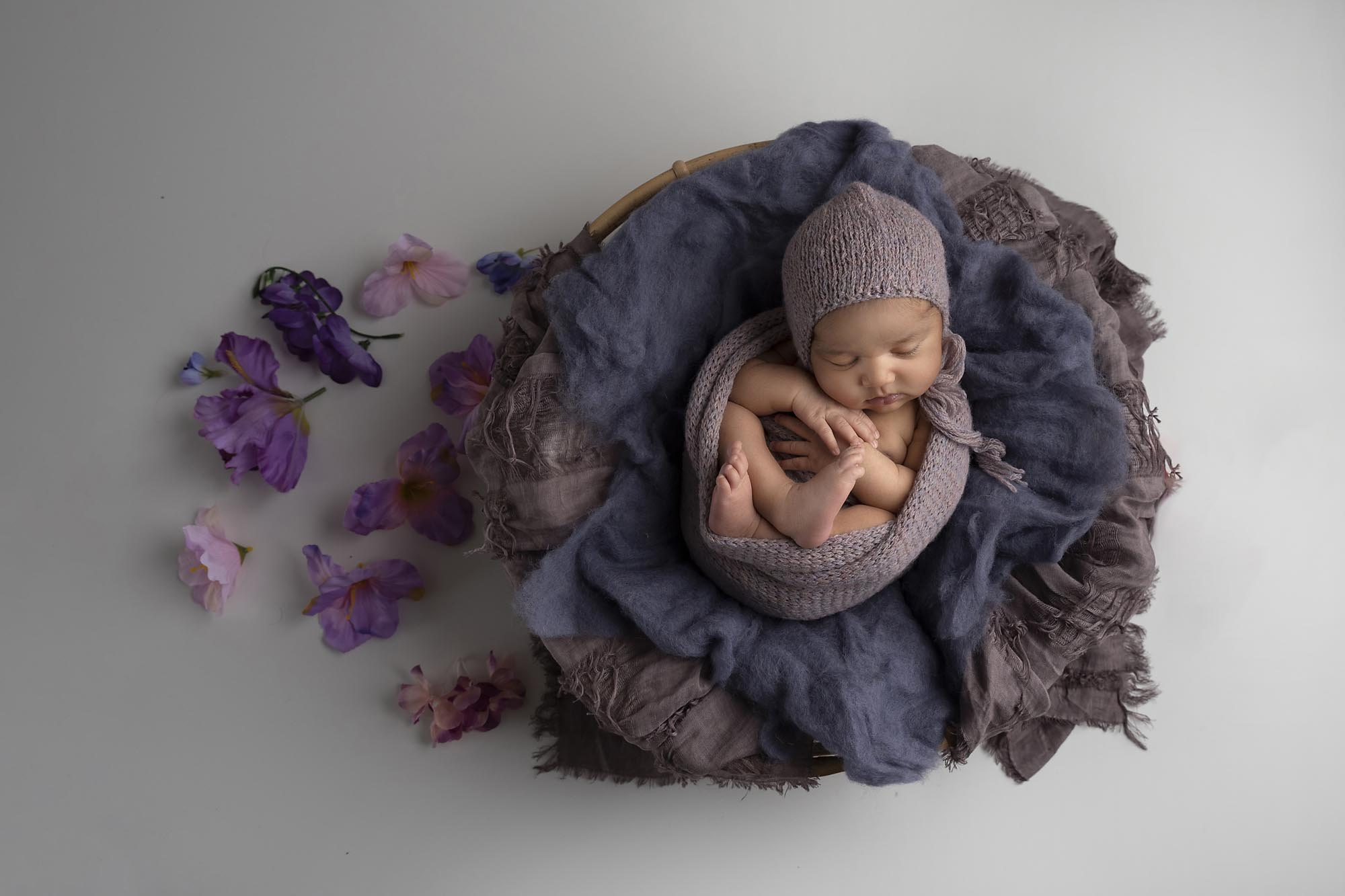 newborn girl with lilac flowers photographed by Newborn Photographer Cheshire