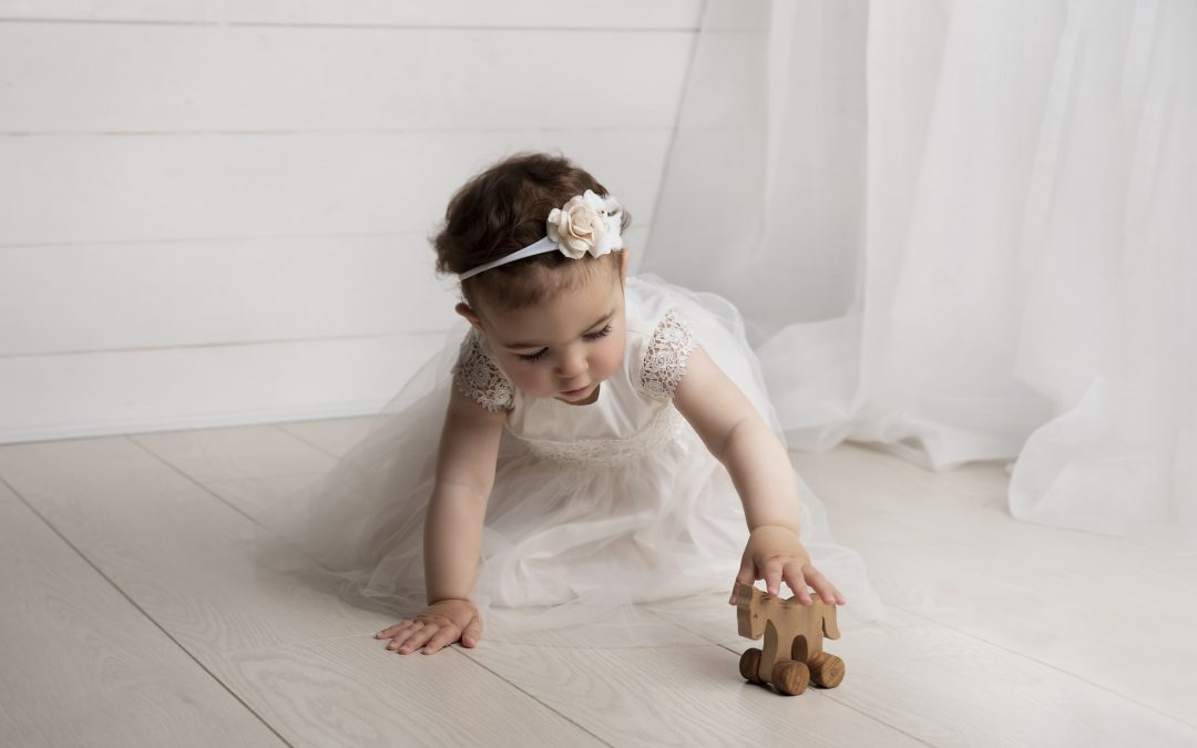 toddler girl sitting playing in front of the window curtain photographed by Baby Photographer Manchester