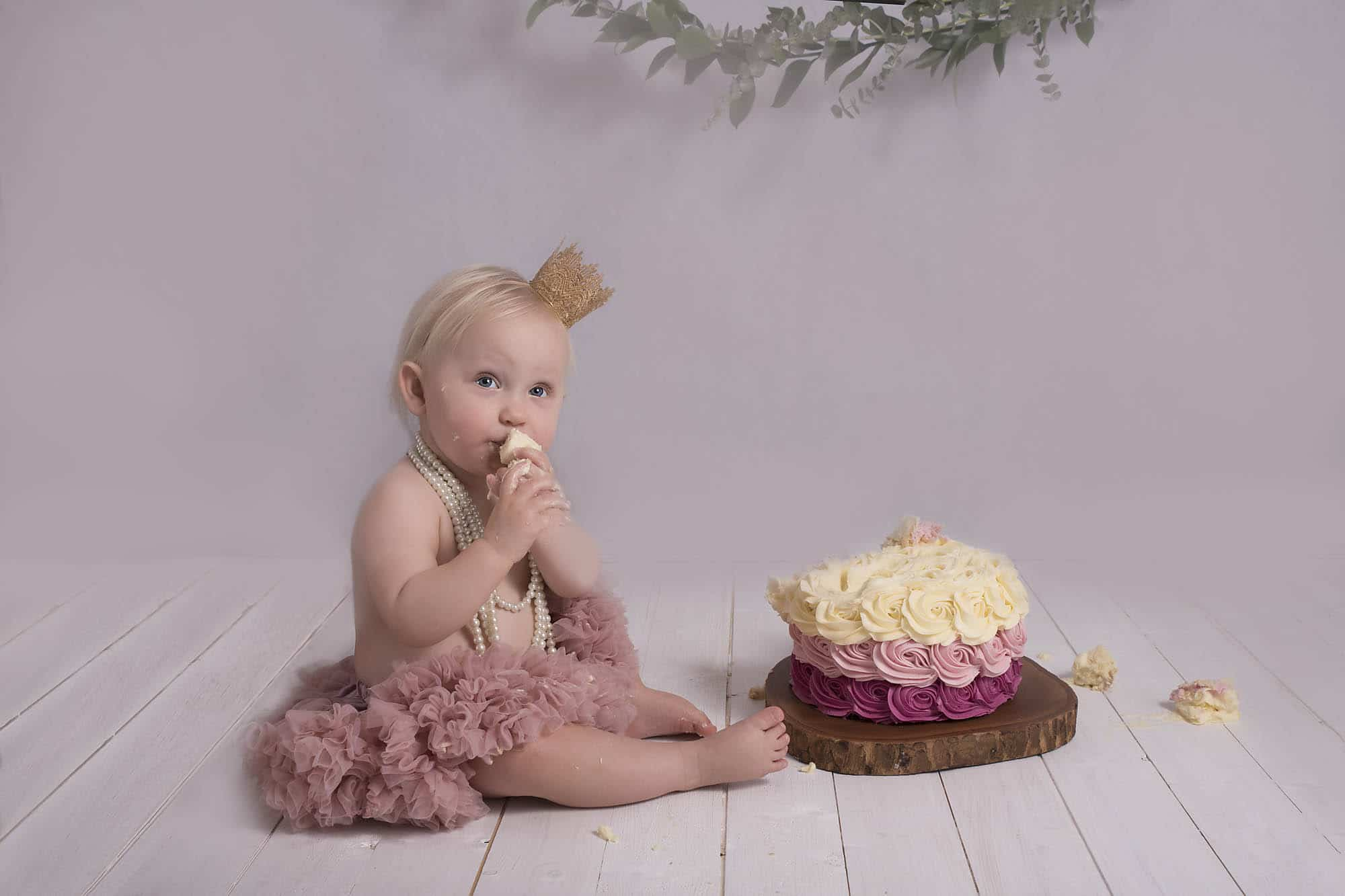 Cakesmash with little girl wearing a crown photographed by cake smash photography Manchester
