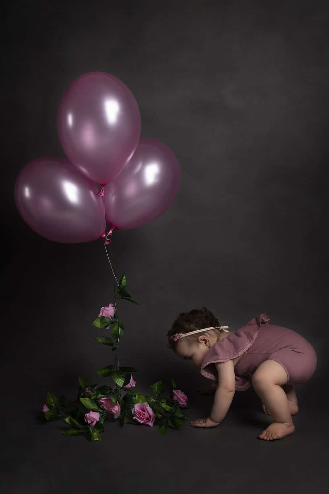 one year old baby girl with baloons photographed by cake smash photography Manchester