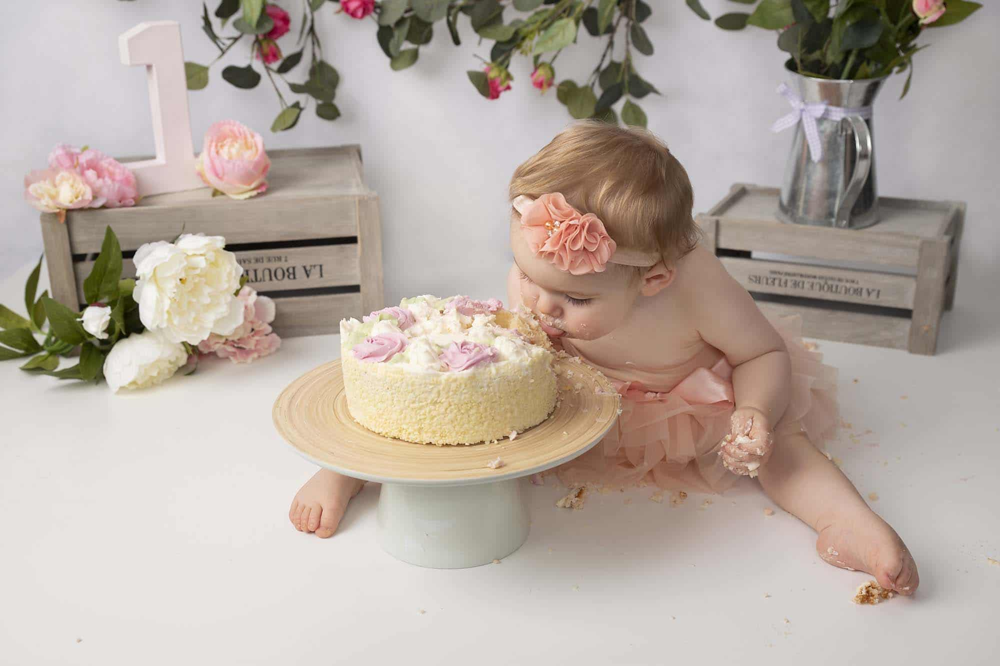 One year old little girl eating a cake photographed by cake smash photography Manchester