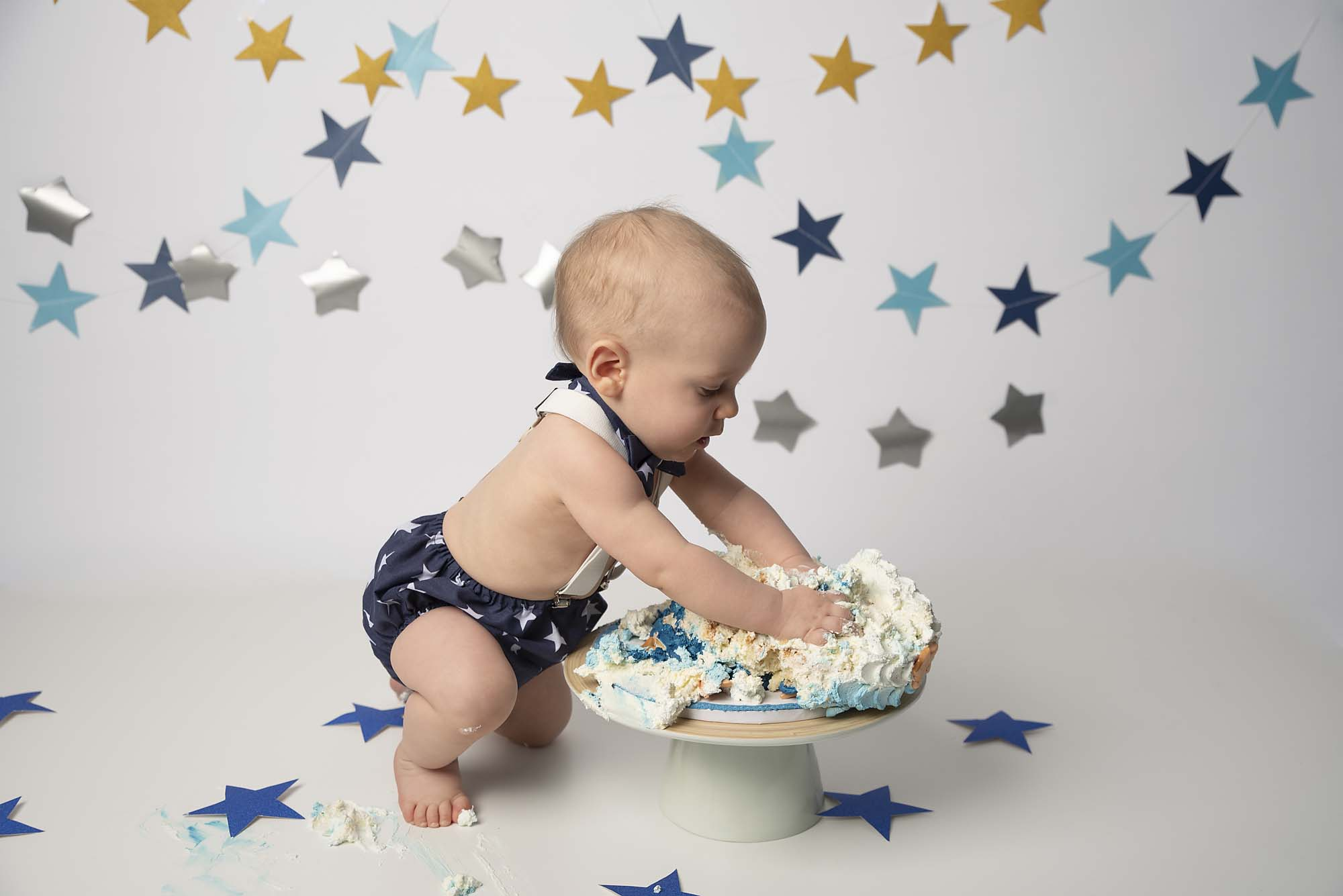 baby boy smashing cake photographed by cake smash photography Manchester