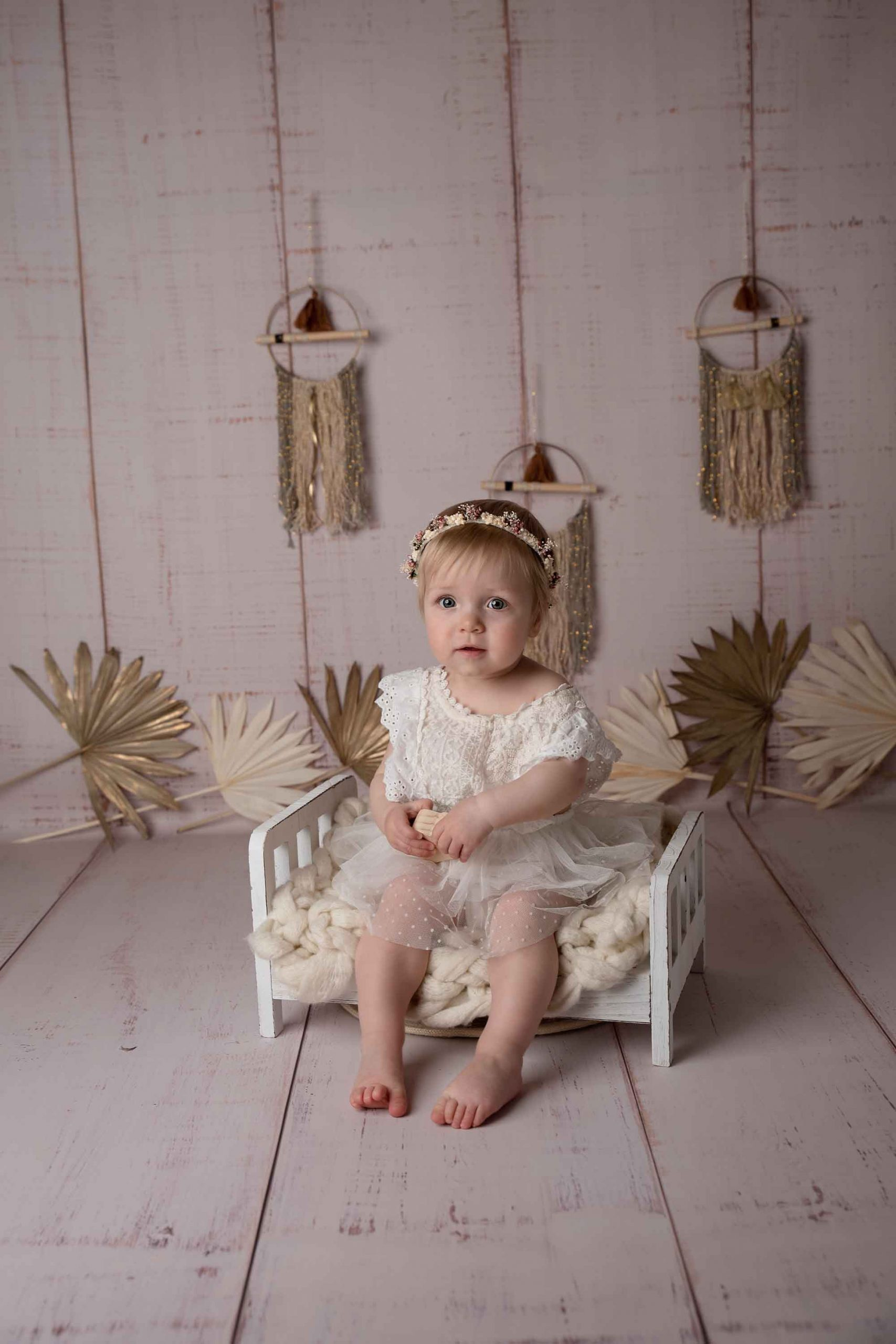 one year old little girl is sitting on a bed with white dress by baby photography Manchester