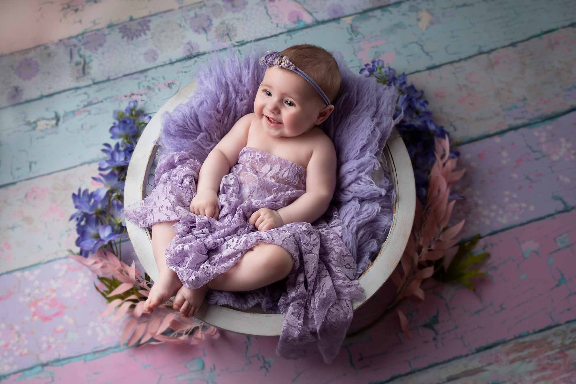 little girl is in a white bowl and purlple fur smiling by baby photogrpahy Manchester