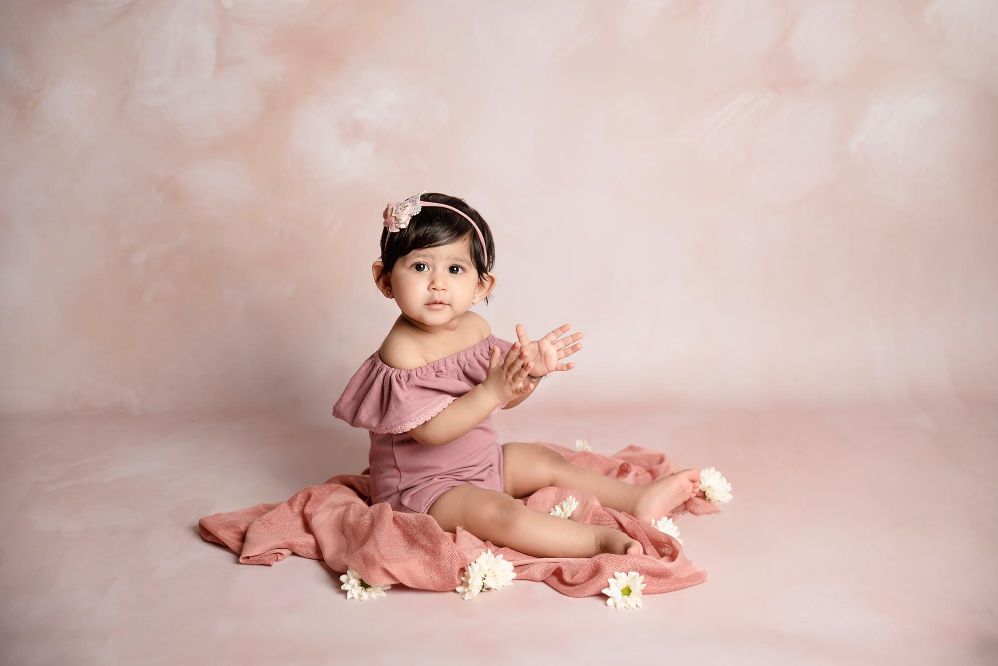 sitter little girl with peachy floral background taken by baby photography Manchester