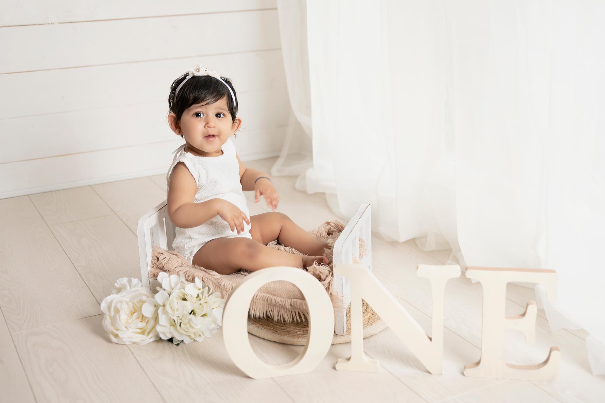 baby portrait in whit dress by the window taken by baby photography Manchester