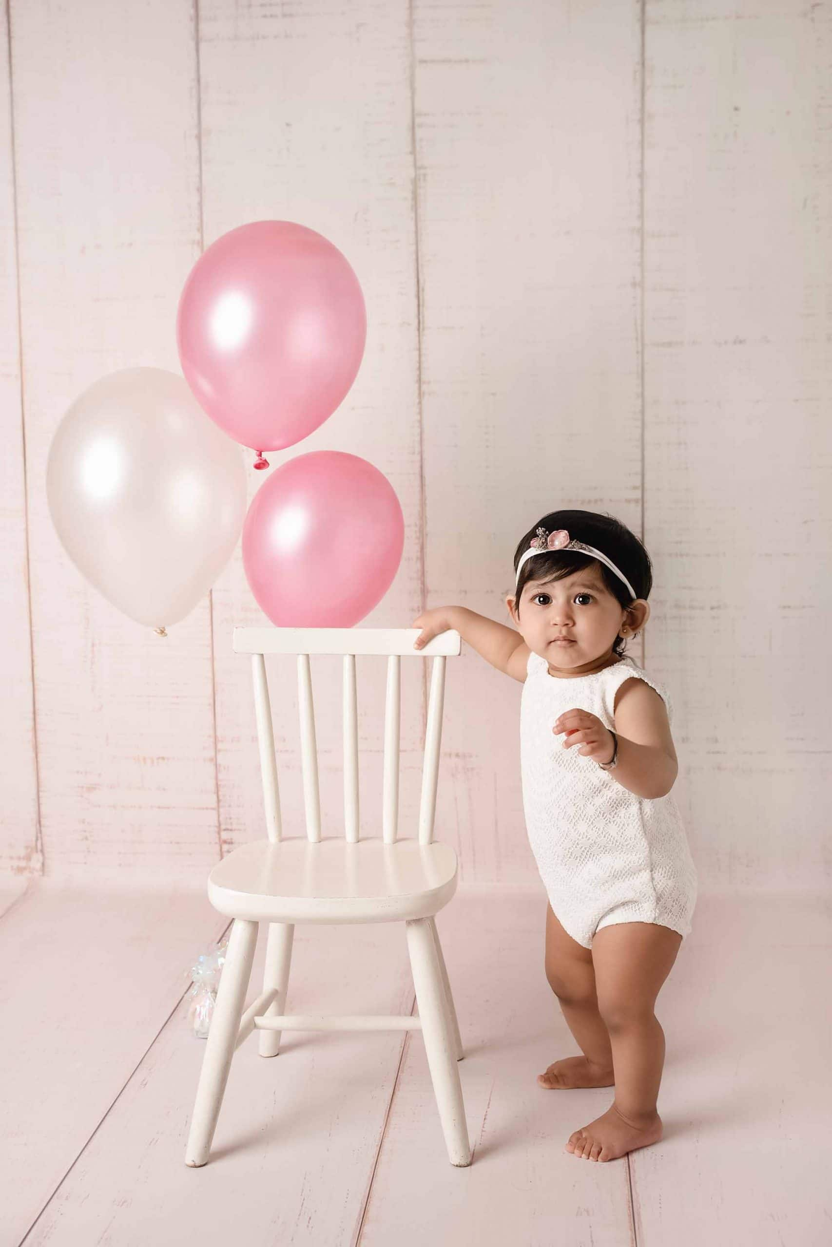 baby girl is standing next to a chair and baloons taken by baby photography Manchester