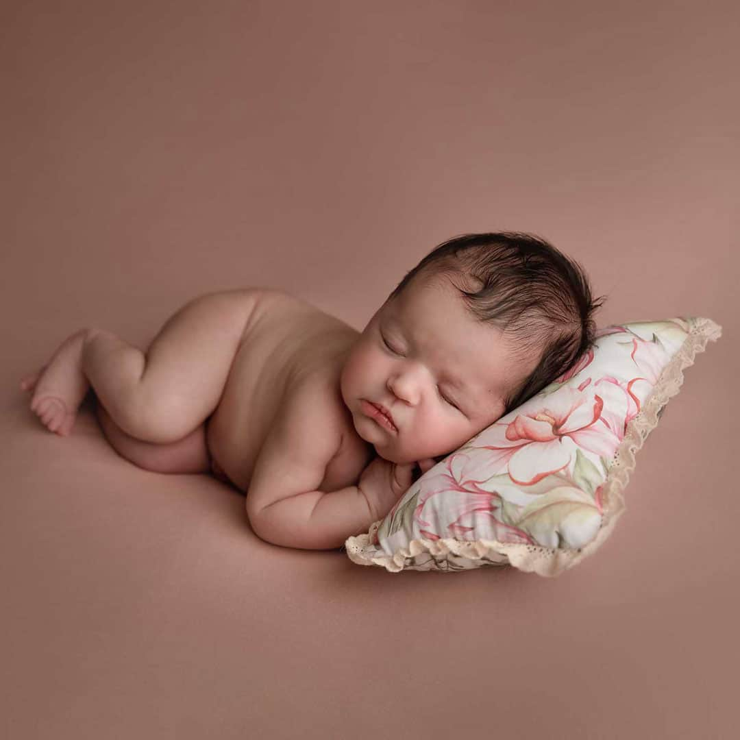newborn baby girl is sleeping on the pilow taken by newborn photography manchester